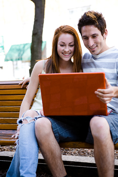 Boy and girl working on laptop